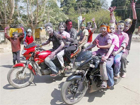 boys driving in motorcycles during holi festival
