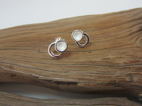 Unusual sterling silver studs with a concave centred satin finish circle attached to a polished silver outline. They sit with the circles next to each other and measure about 12mm across.