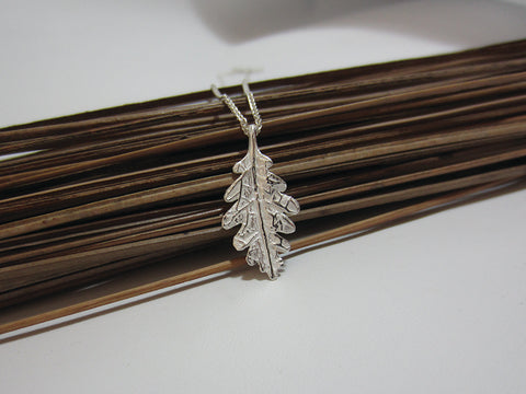 A symbol of courage and power this sterling silver oak leaf pendant measures 25mm ong and 15mm wide. It is shown here on a spiga chain which really complements the slightly satin finish. 925 Silver Canterbury