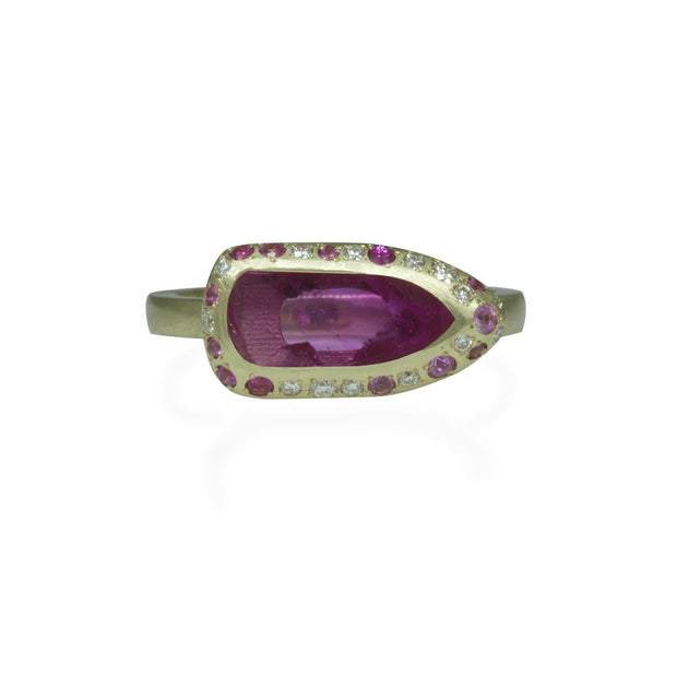 Top view of green gold ring. Center stone is a rough pink spinel slab. Bezel contoured with white and pink diamonds and pink sapphires smalls. Green gold ring shank has a matte finish.