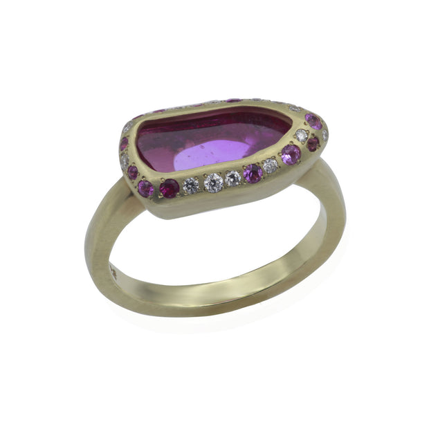 Three-quarter view of green gold ring. Center stone is a rough pink spinel slab contoured by a shield-shaped bezel with white and pink diamonds and pink sapphires smalls around. Green gold ring shank has a matte finish.