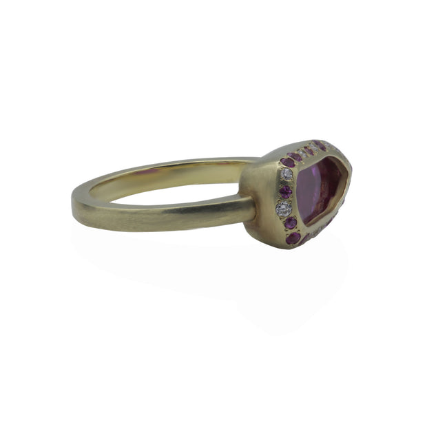 Side view of green gold ring. Center stone is a rough pink spinel slab contoured by a shield-shaped bezel with white and pink diamonds and pink sapphires smalls around. Green gold ring shank has a matte finish.
