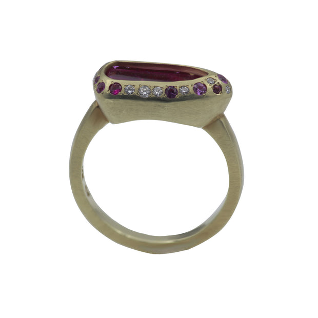 Through finger view of green gold ring. Center stone is a rough pink spinel slab contoured by a shield-shaped bezel with white and pink diamonds and pink sapphires smalls around. Green gold ring shank has a matte finish.