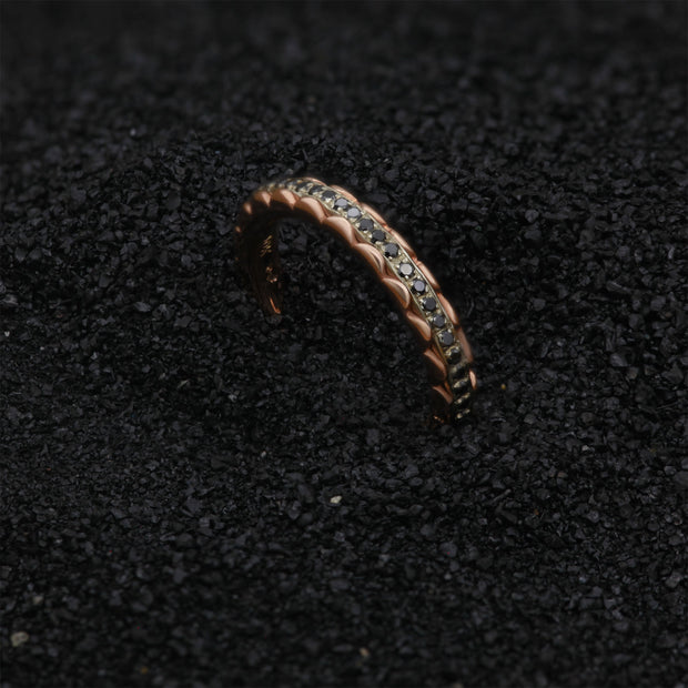 top view of wedding band with 2 rose colored petal shaped rings encasing a white gold band with black diamond stones set all the way around. The ring is seated in black sand.