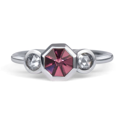 Front view of 3 stone white gold ring. Center stone is an octagonal pink center stone that is bezel-set. There are 2 round rose cut diamonds, bezel set on either side of center stone.