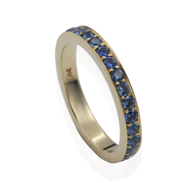 Three quarter view of yellow gold band with blue sapphires bead set all the way around.