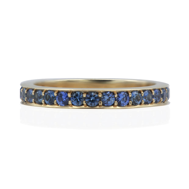 Front view of yellow gold band with blue sapphires bead set all the way around.