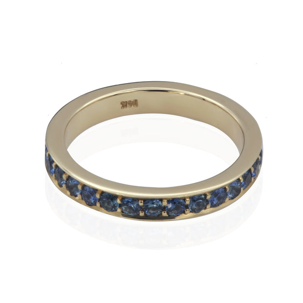 Plunging front view of yellow gold band with blue sapphires bead set all the way around.