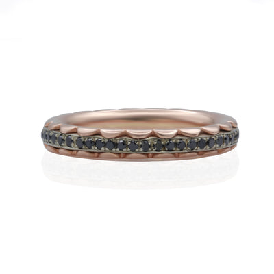 Front view of 2 rose colored petal shaped rings encasing a white gold band with black diamond stones set all the way around.