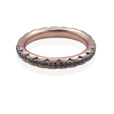 Plunging front view of 2 rose colored petal shaped rings encasing a white gold band with black diamond stones set all the way around.