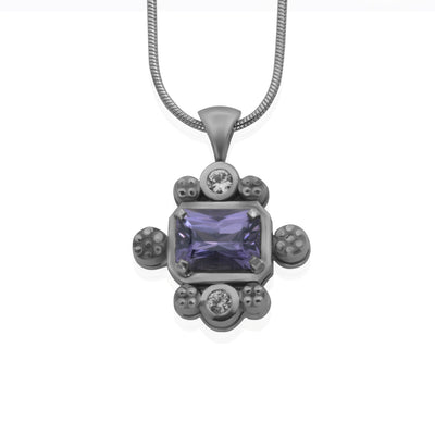 Front view of white gold pendant with purple rectangular shaped stone in the center. Pendant sprinkled with decorative circular shapes around center stone. Showcased on a white gold snake chain