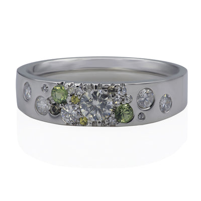 Front view of white metal ring with scattered white diamonds, scattered green sapphires and scattered yellow sapphires.