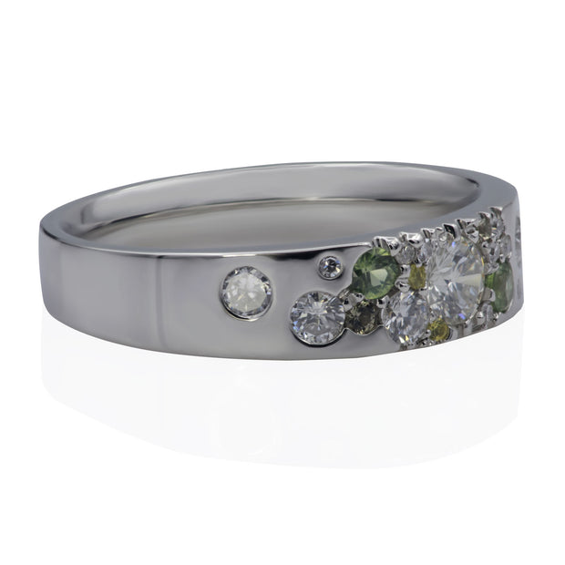 Left side view of white metal ring with scattered white diamonds, scattered green sapphires and scattered yellow sapphires.