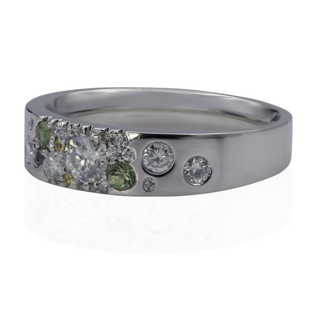 Right side view of white metal ring with scattered white diamonds, scattered green sapphires and scattered yellow sapphires.