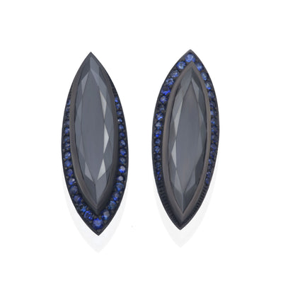 Front view of dark silver stud earrings. Center stones are metallic black. Shaped like a marquis with dark blue sapphires contouring.