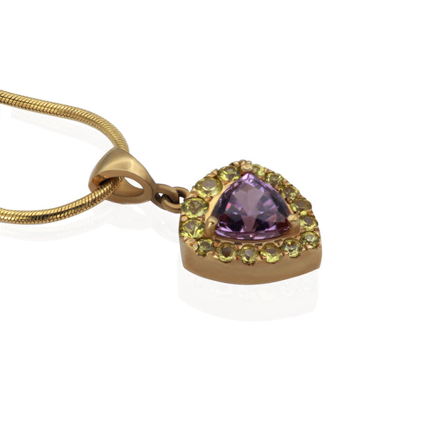 plunging side view of yellow gold necklace and pendant. Pendant is trillion shaped with a trillion shaped purple stone in the center and small round yellow stones surrounding center stone like a halo.