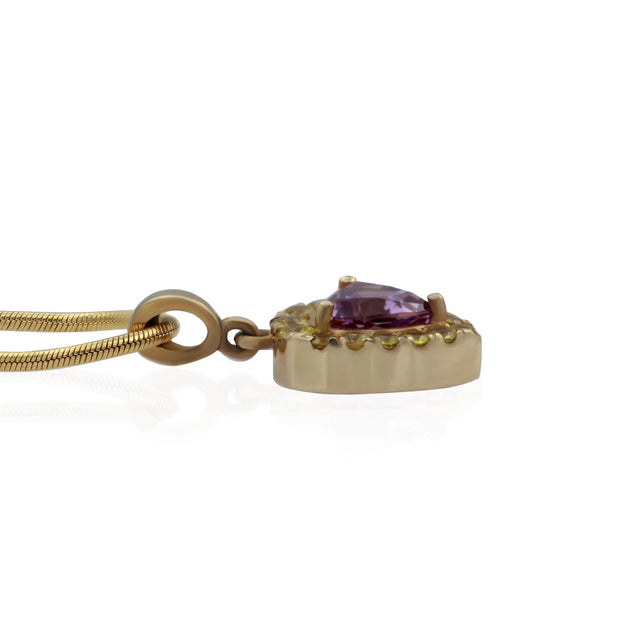 Flat side view of yellow gold necklace and pendant. Pendant is trillion shaped with a trillion shaped purple stone in the center and small round yellow stones surrounding center stone like a halo.