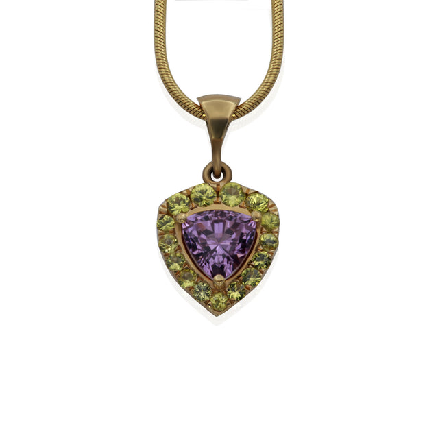 Front view of yellow gold necklace and pendant. Pendant is trillion shaped with a trillion shaped purple stone in the center and small round yellow stones surrounding center stone like a halo.