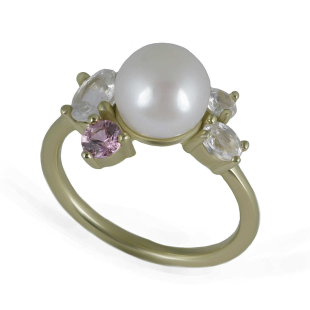 Janine de Dorigny pearl ring. Three-quarter view of 8mm pearl featured in the center of yellow gold ring, surrounded by one round pink sapphire and 3 white sapphires of varying sizes and shapes.