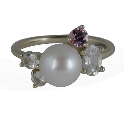Janine de Dorigny pearl ring. Top view of 8mm pearl featured in the center of yellow gold ring, surrounded by one round pink sapphire and 3 white sapphires of varying sizes and shapes.