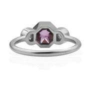 Back view of 3 stone white gold ring. Center stone is an octagonal pink center stone that is bezel-set. There are 2 round rose cut diamonds, bezel set on either side of center stone.