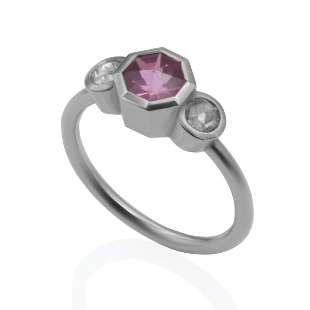 Three-quarter view of 3 stone white gold ring. Center stone is an octagonal pink center stone that is bezel-set. There are 2 round rose cut diamonds, bezel set on either side of center stone.