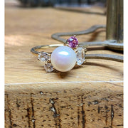 Janine de Dorigny pearl ring. Top view of 8mm pearl featured in the center of yellow gold ring, surrounded by one round pink sapphire and 3 white sapphires of varying sizes and shapes. Ring displayed on wooden bench top.