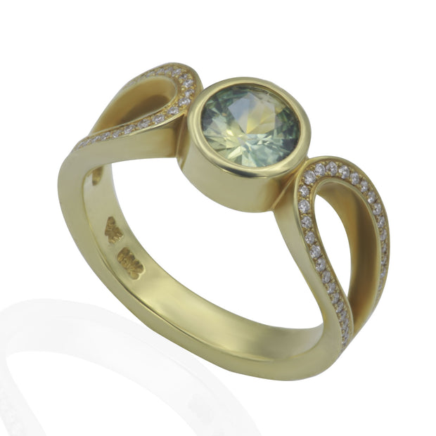 Side view of green gold ring with pale blue bezel set sapphire in the center and an elongated loop on each side of center bezel with bead set diamond smalls