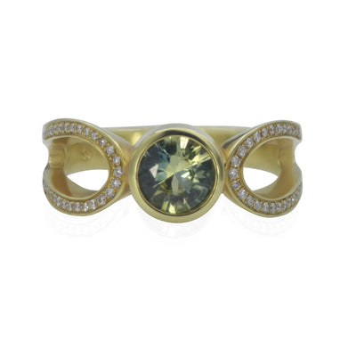 Front view of green gold ring with pale blue bezel set sapphire in the center and an elongated loop on each side of center bezel with bead set diamond smalls