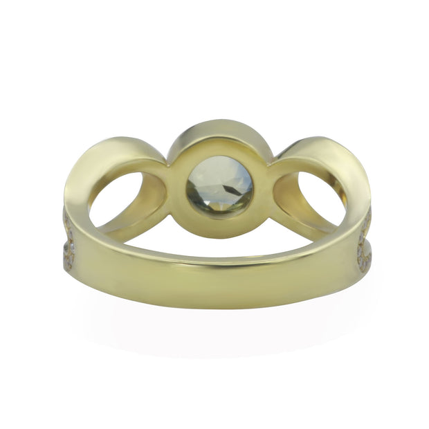 Back view of green gold ring with pale blue bezel set sapphire in the center and an elongated loop on each side of center bezel with bead set diamond smalls