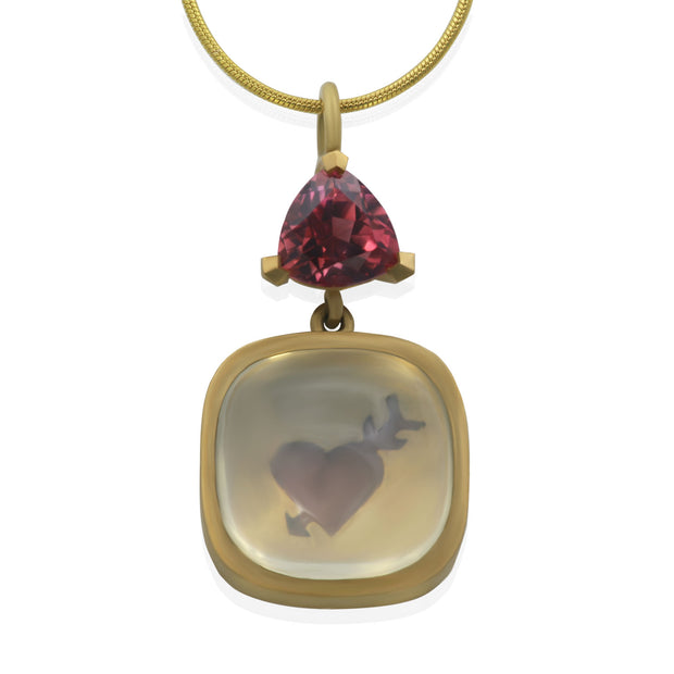 Front view of yellow gold pendant. Pink trillion shaped stone at top and beneath a translucent white square shaped cabochon with a red heart pierced by an arrow painted below the stone. Showcased on a yellow gold snake chain.