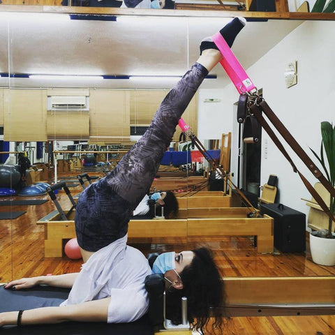 Pilates Enthusiast Doing Short Spine On A Pilates Reformer With Good Citizen Pilates Straps