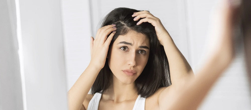 Woman facing a mirror, worried about her hair