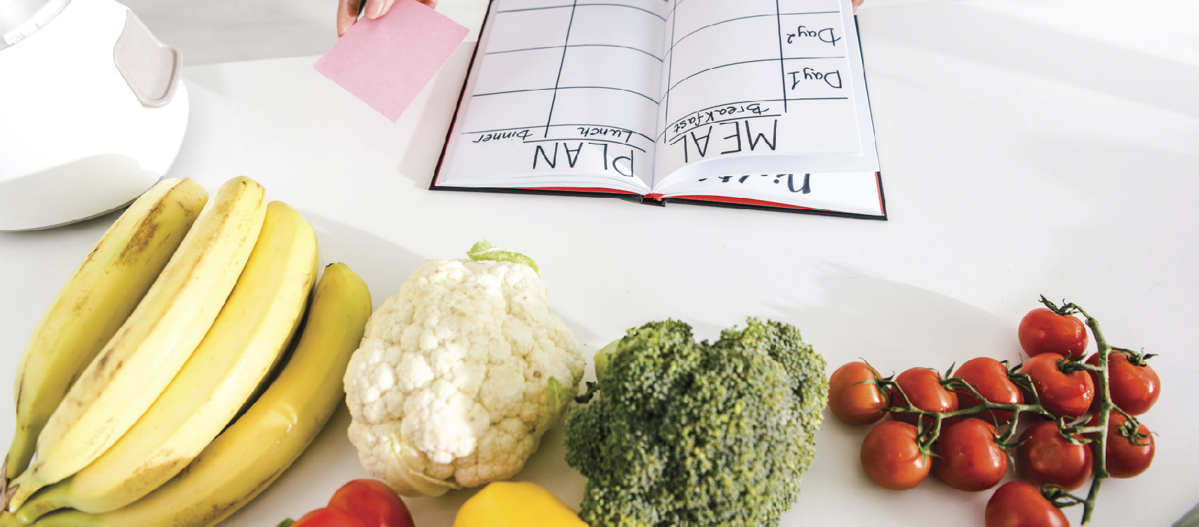 A meal planner with fruits and vegetables on the side