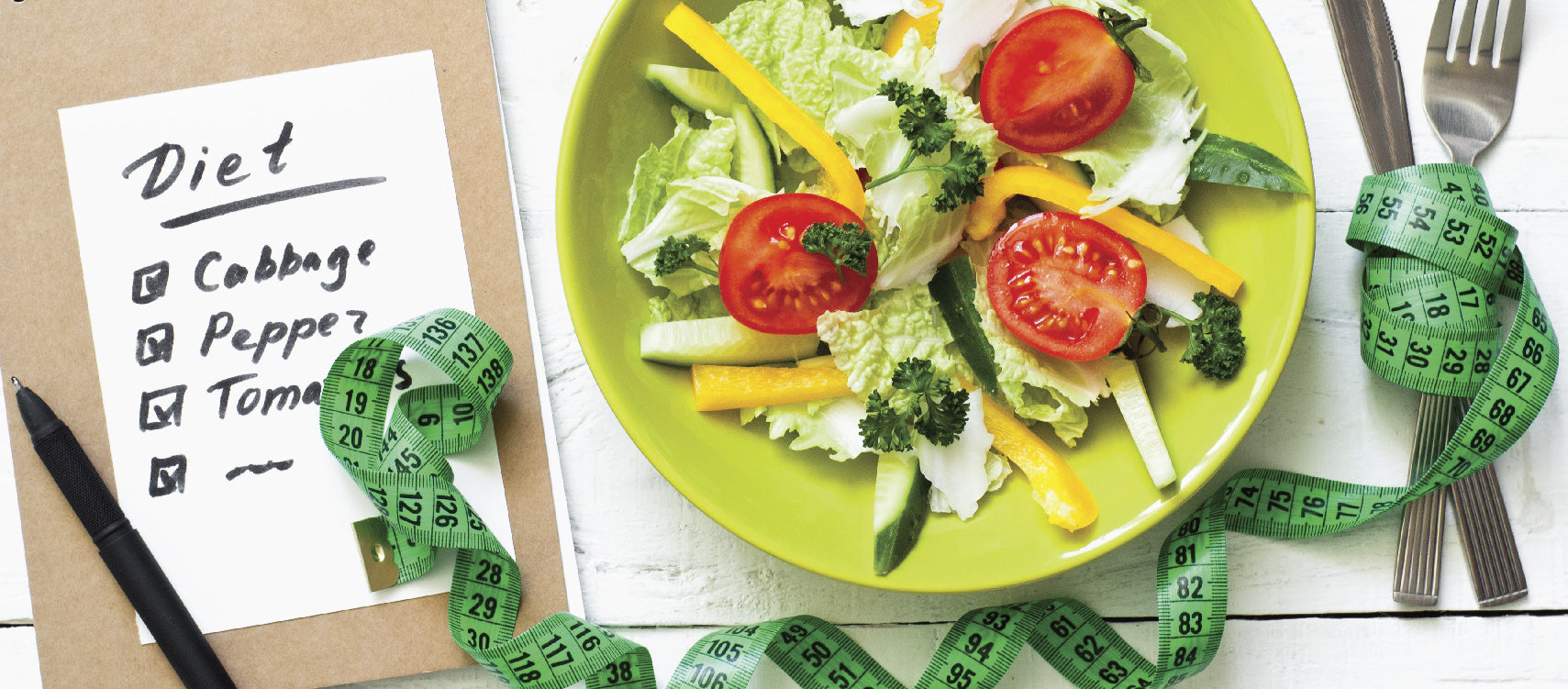 Diet list with plate of salad and a tape measure