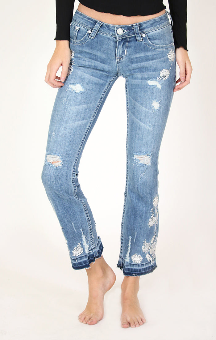 Medium wash, bootcut jeans with distressing, white floral embroidered design, and an unfinished hem