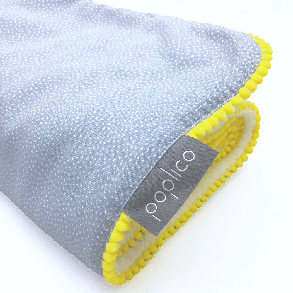 Pompon rimmed baby Blanket with teddy fur fabric on reverse. Size 90 x 70 cm. Machine Washable