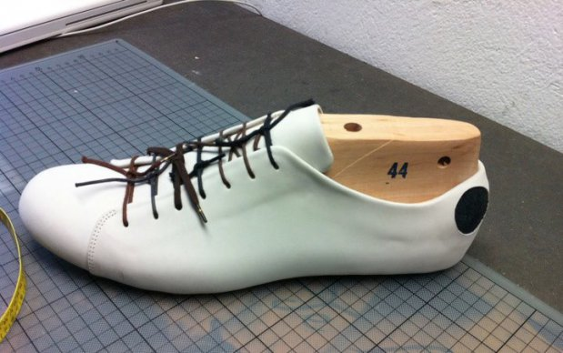Cream Atheist shoe being stretched on a wooden last.