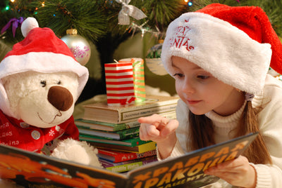 child in christmas hat with teddy bear