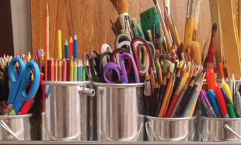 Scissors, paintbrushes, colored pencils, and markers in tin buckets.