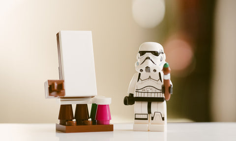 Stormtrooper Lego guy with paintbrush, easel, and paints.