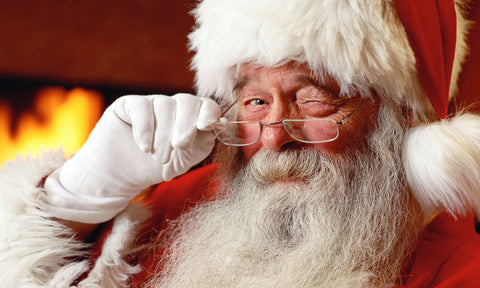 Santa Claus winking and looking over his glasses.
