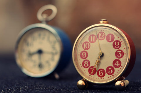 Two vintage-style alarm clocks, one is red and one is blue.