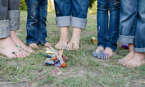 A family's feet, pant cuffs, and paintbrushes covered with paint