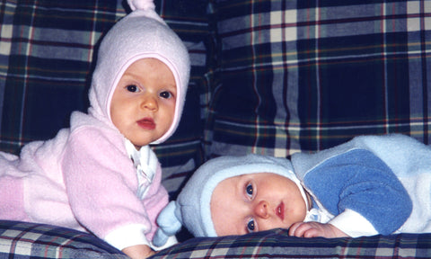 Boy-girl baby twins, dressed in pink and blue, laying on a couch.