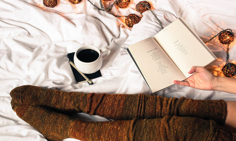 Legs in wool socks relaxing on a bed with coffee and a book.