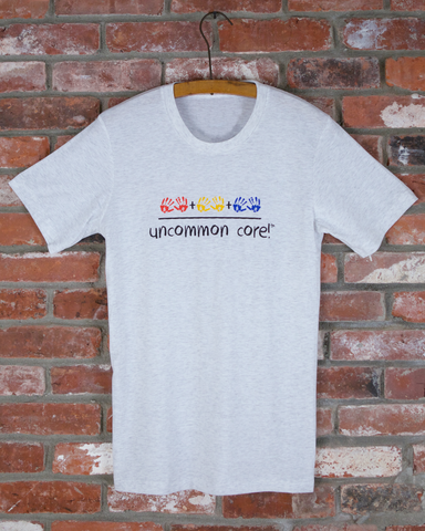 "White men's short sleeve t shirt with colorful handprints and ""uncommon core!"""