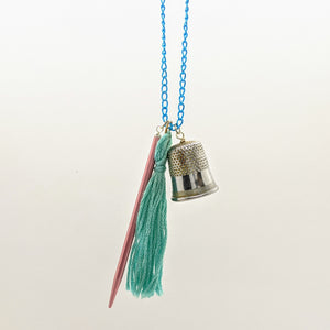 Pink and blue pointed needle, thimble, and tassel knitting needle necklace