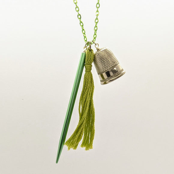 Green pointed needle, thimble, and tassel knitting needle necklace