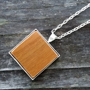 Photo of wooden flooring sample silver-plated necklace from above
